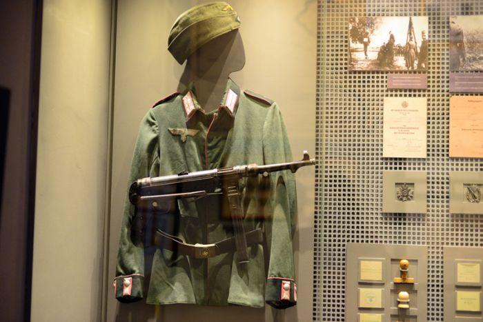 Форма военнослужащего немецкой полевой жандармерии. Справа — фотографии зверств гитлеровцев, образцы печатей для документов
